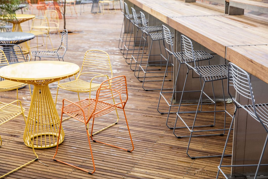A fine-lined steel profile gives the Jak Barstool - a premium outdoor metal barstool - an elegant form and visually weightless quality.